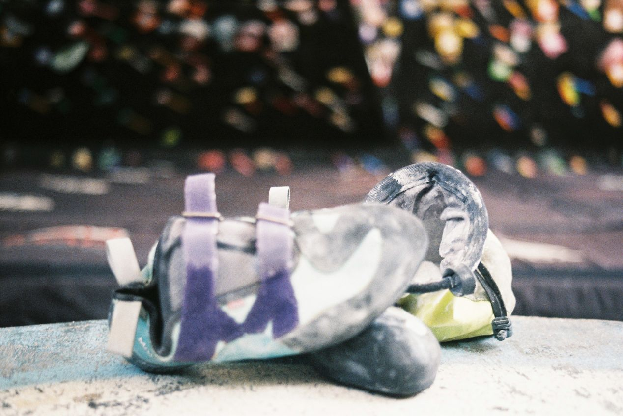 Climbing shoes and a chalk bag, bouldering essentials. The climbing wall is in the background. Shot with Canon QL25 on Fujicolor 200.