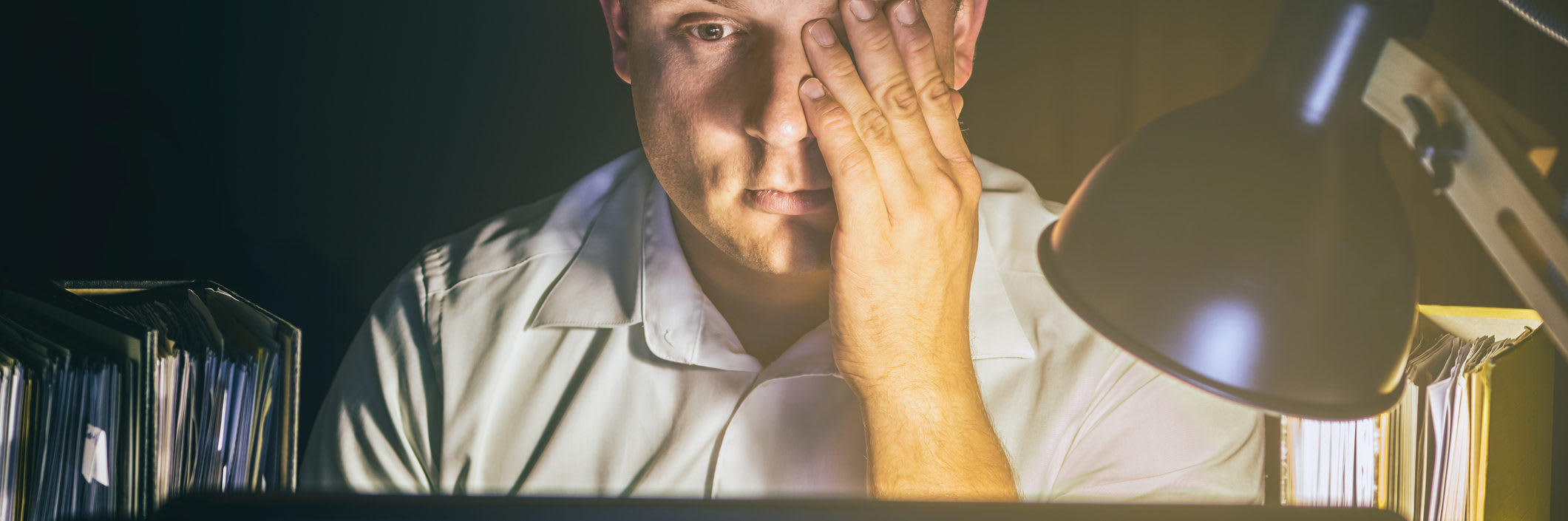 main image - Man with tired eyes due to too much work on the computer screen
