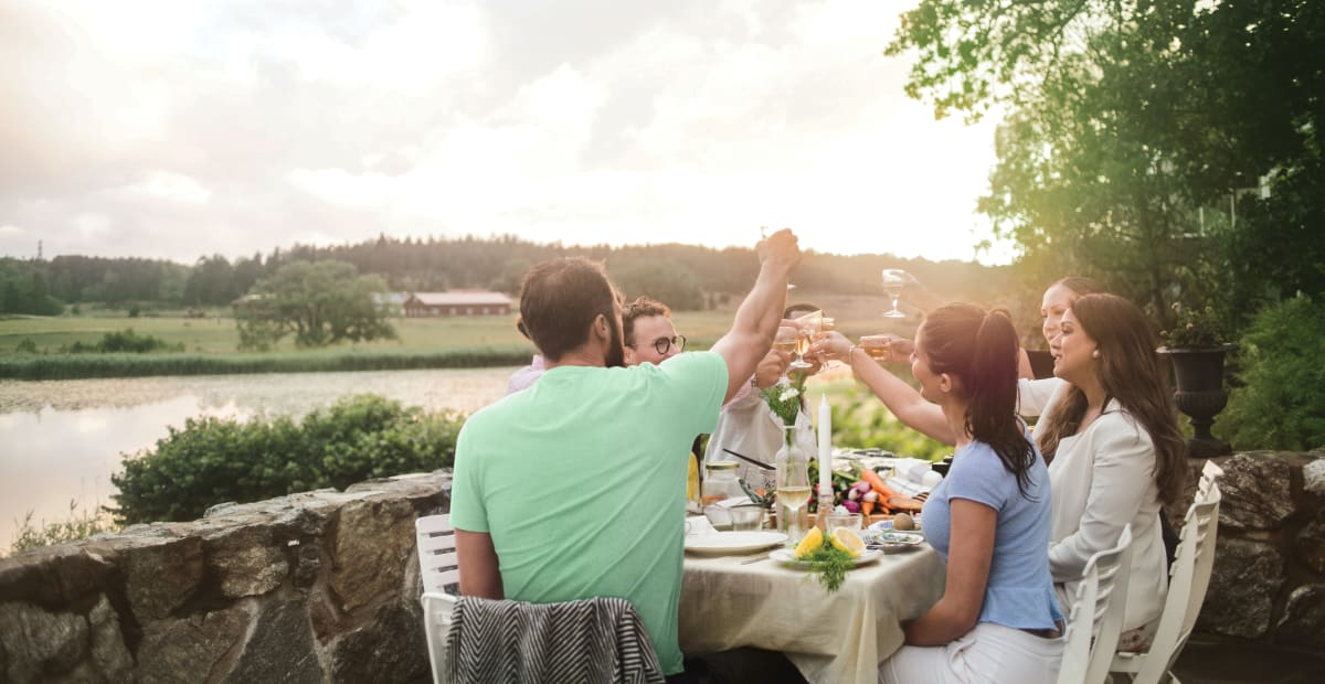 Anora - About us hero image - people having dinner in a garden