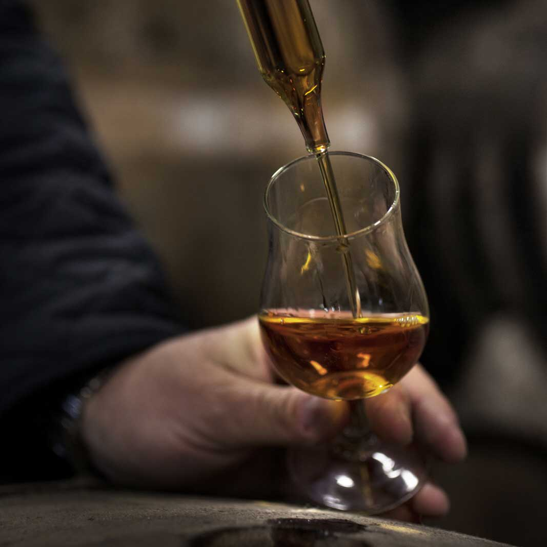 Pouring cognac to glass with pipette