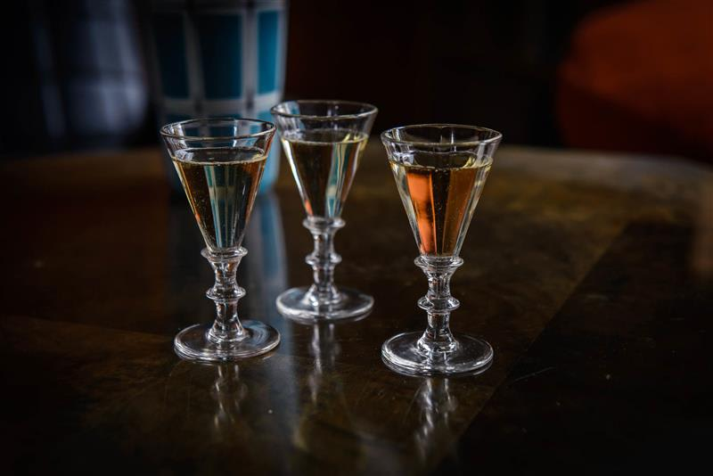 Three schnapps glasses on a wooden table