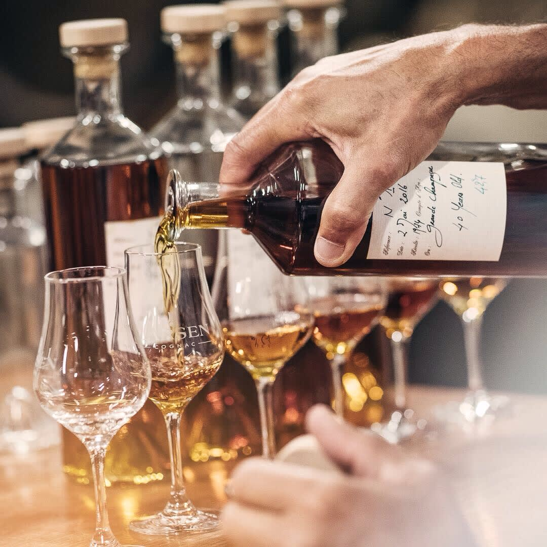 Pouring Larsen cognac from an old bottle to glasses