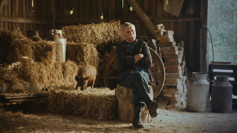 Koskenkorva villager sitting on a haystack