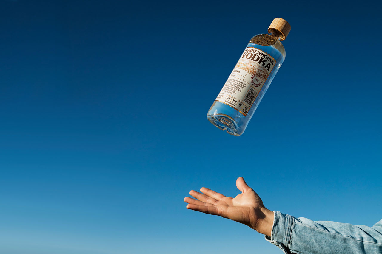Koskenkorva vodka with blue background and a hand