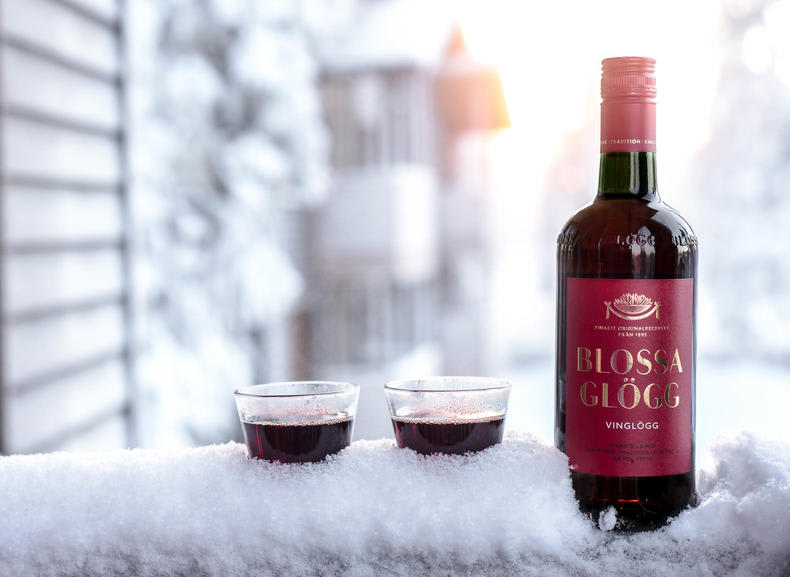 Two Blossa Vin Glögg glasses and bottle in snow