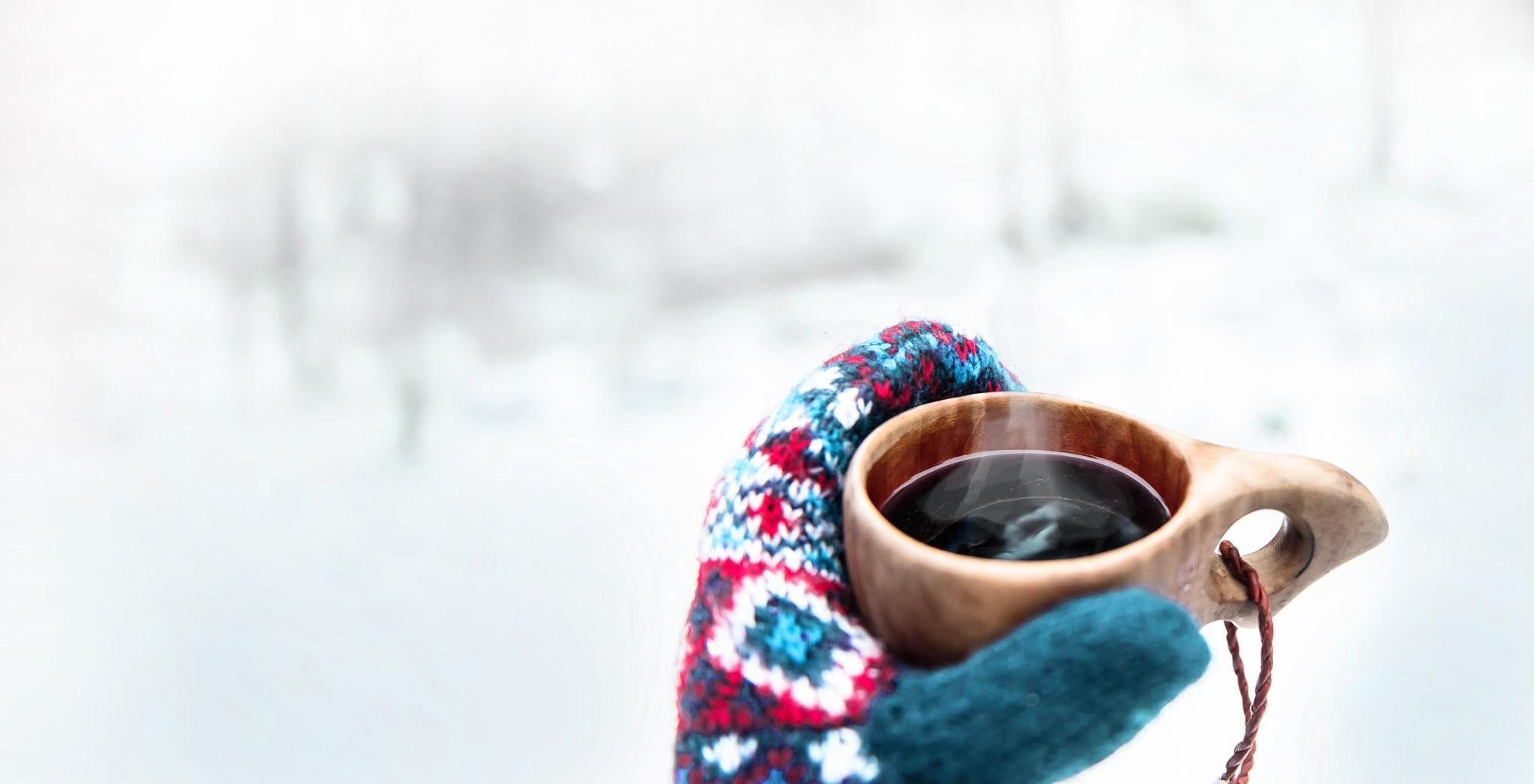 Heißes Getränk in Kuksa in Händen