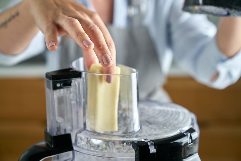 Grate butter into food processor