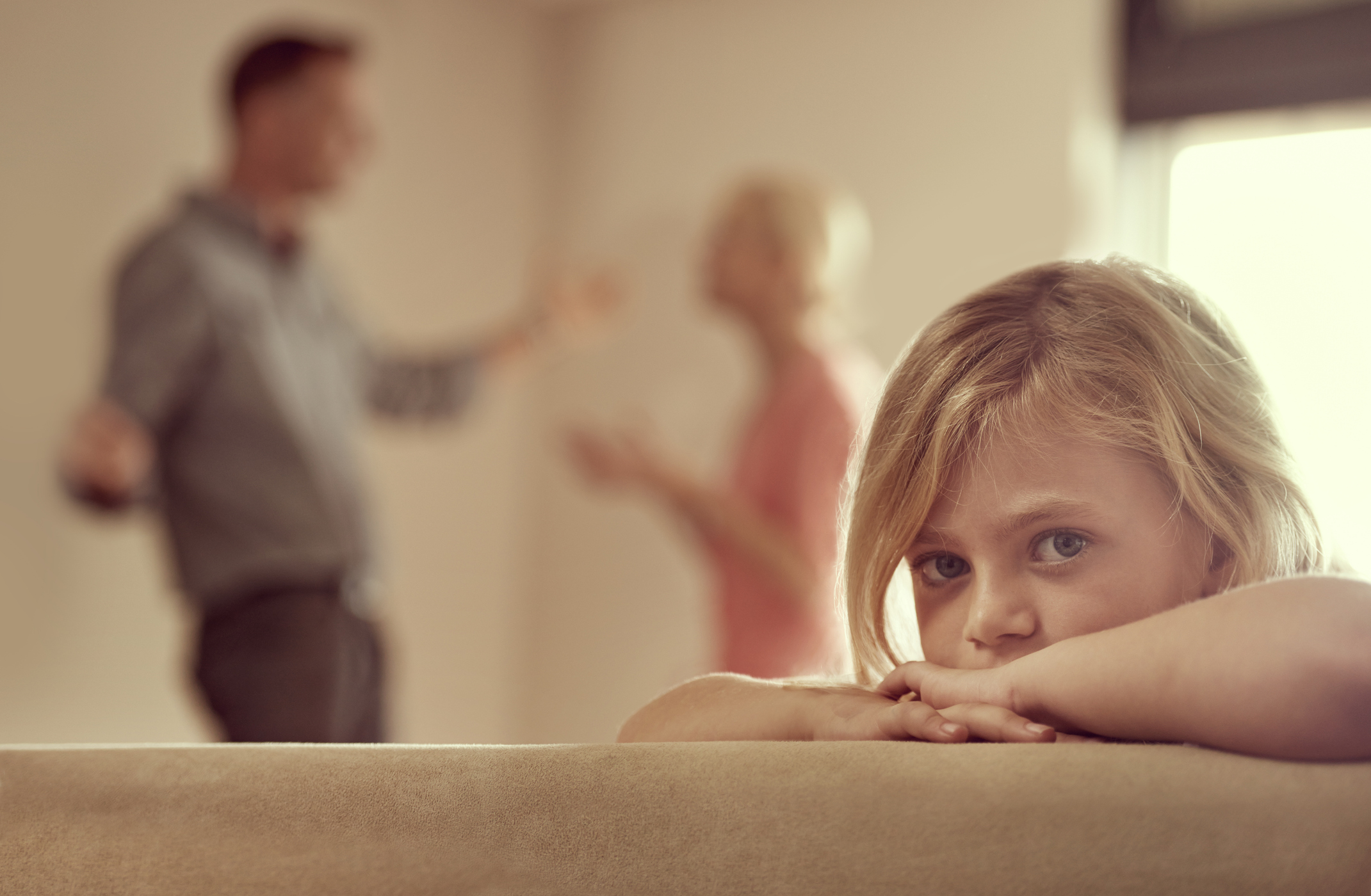 Sad little girl looks into camera while parents fight in background