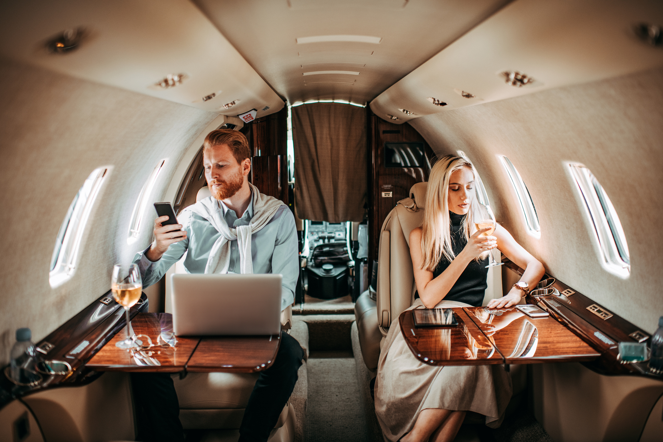 Rich couple ignoring each other on a private plane