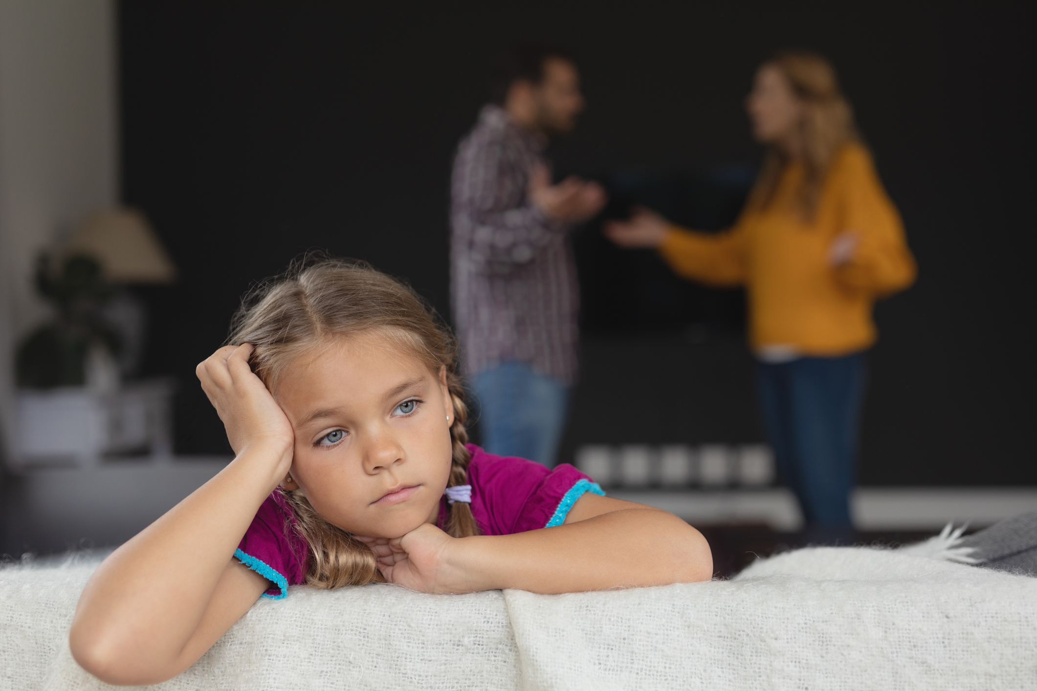 Sad little girl looks off camera while parents fight in background