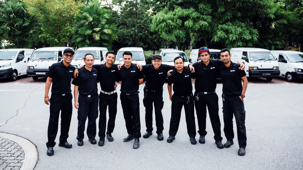 Singapore team standing on a parking lot and smiling