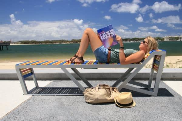 Dívka sedí na lehátku a čte si