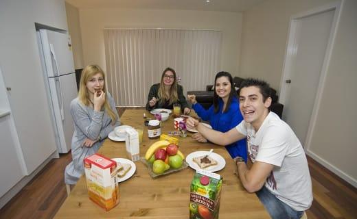 Studenti jedí svačinu u jídelního stolu