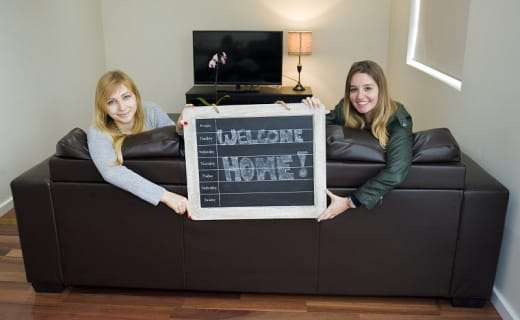 Dvě dívky drží ceduli Welcome Home