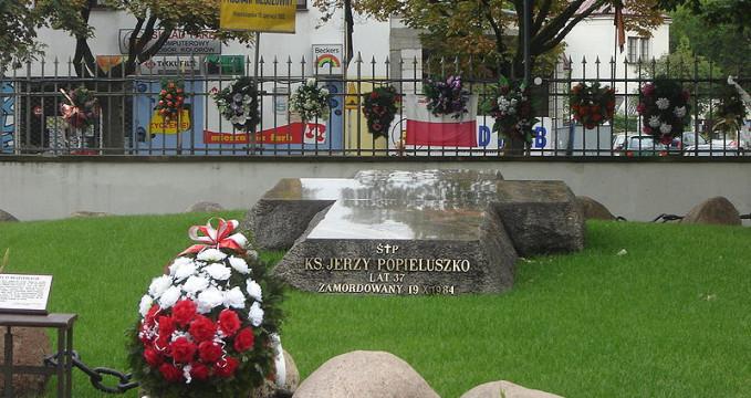 Hrob J. Popieluszky, zahrada kostela sv. Kostki - https://commons.wikimedia.org/wiki/File:Popie%C5%82uszkogr%C3%B3b.JPG