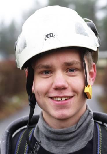 Portrett av ung smilende mann med hvit hjelm på hodet