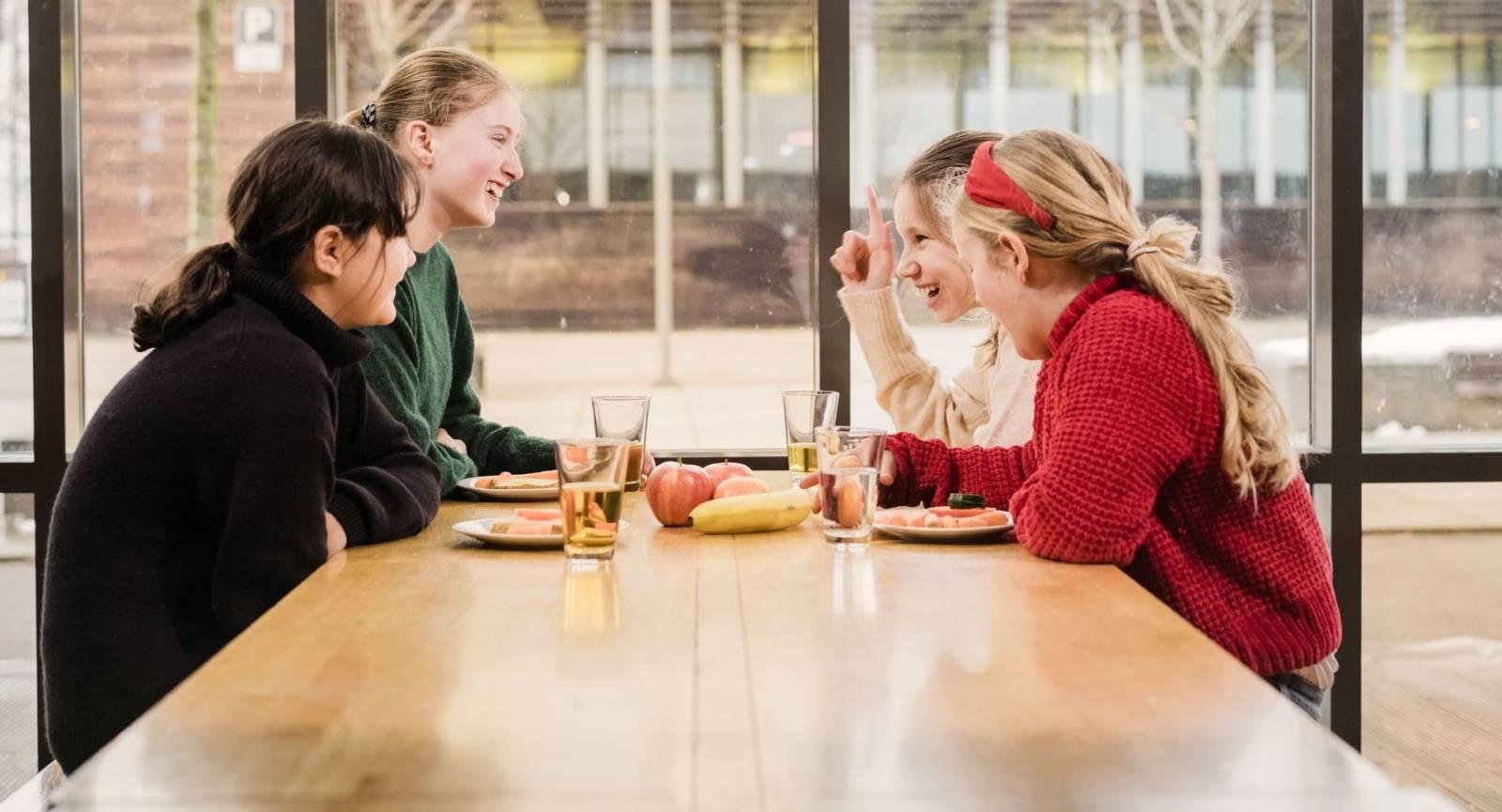 Fire unge jenter sitter smilende rundt et bord. De har tallerkener med brødmat foran og glass med juice foran seg.