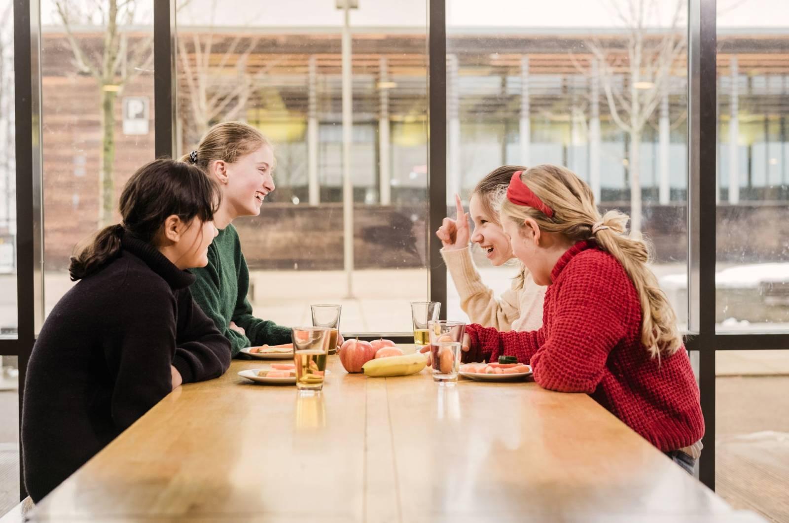 Fire smilende unge jenter sitter i et lyst lokale rundt et bord med mat på asjetter, frukt og glass med drikke.