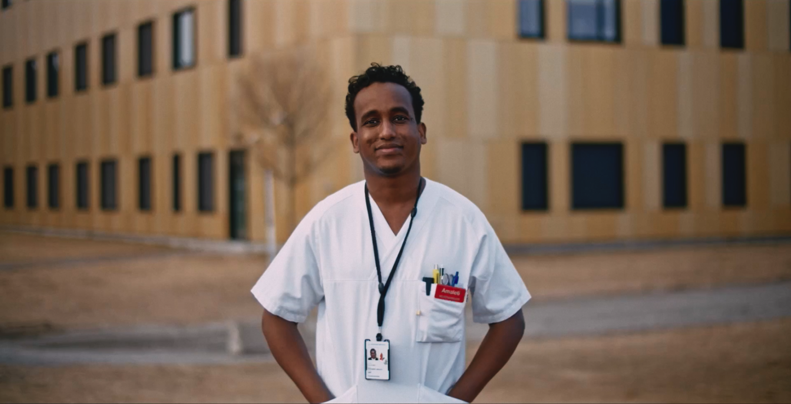 Mann i hvit sykepleieruniform, mørkt hår. Står utendørs.