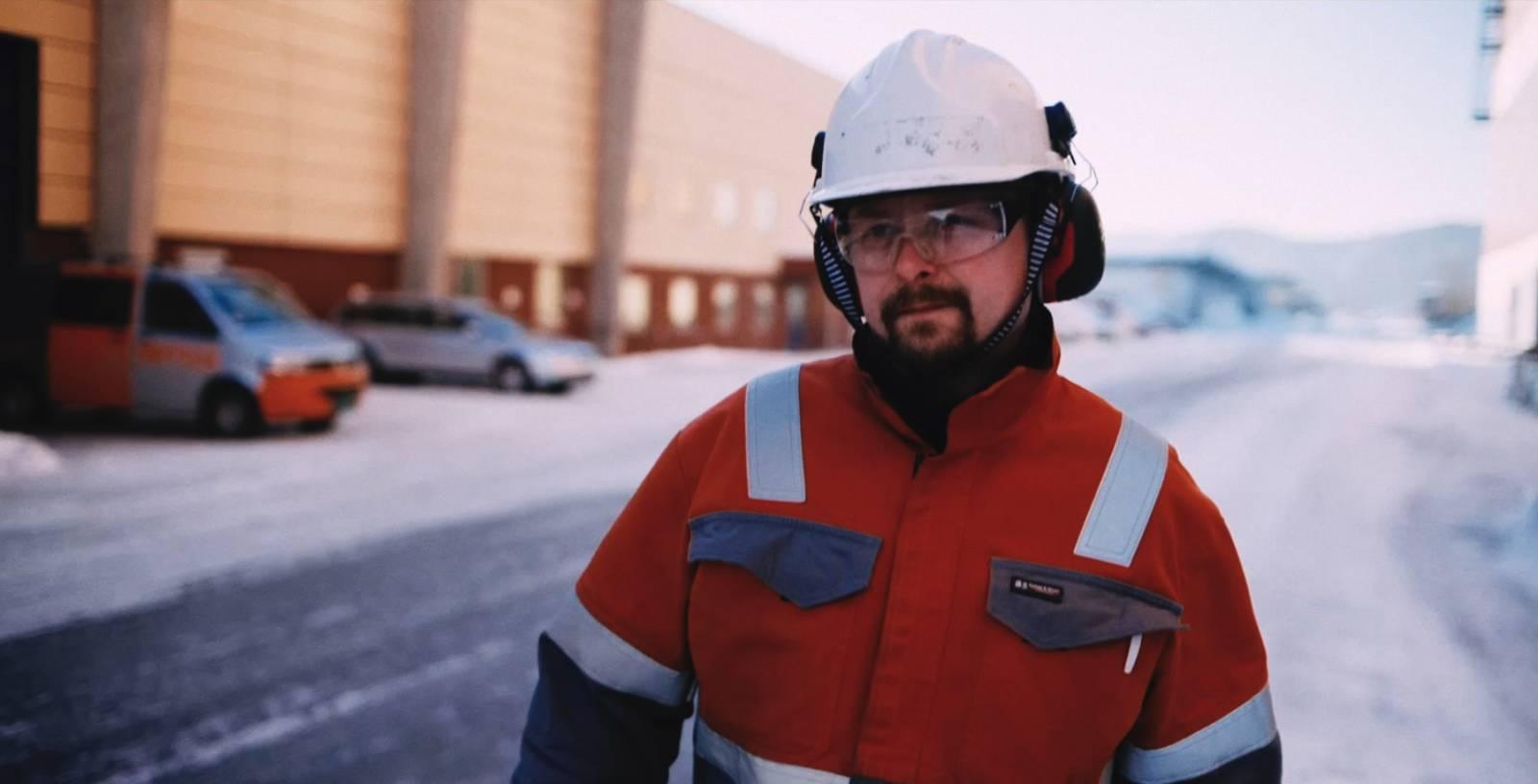 Mann i hvit hjelm og orange kjeledress, går bortover. Utendørs.