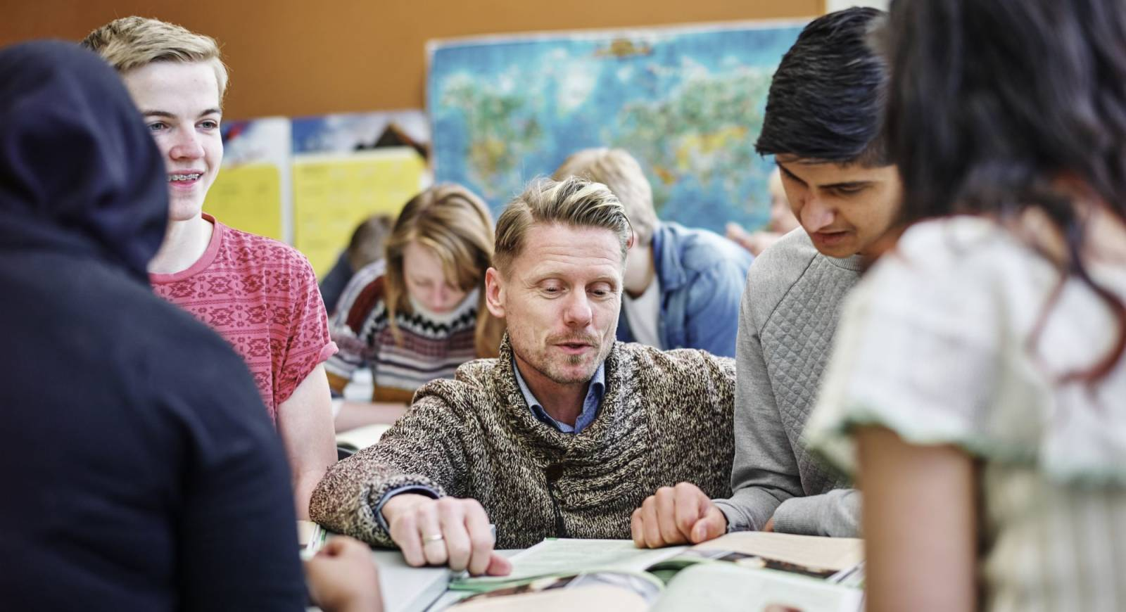 Lærer og elever som ser i bøker.