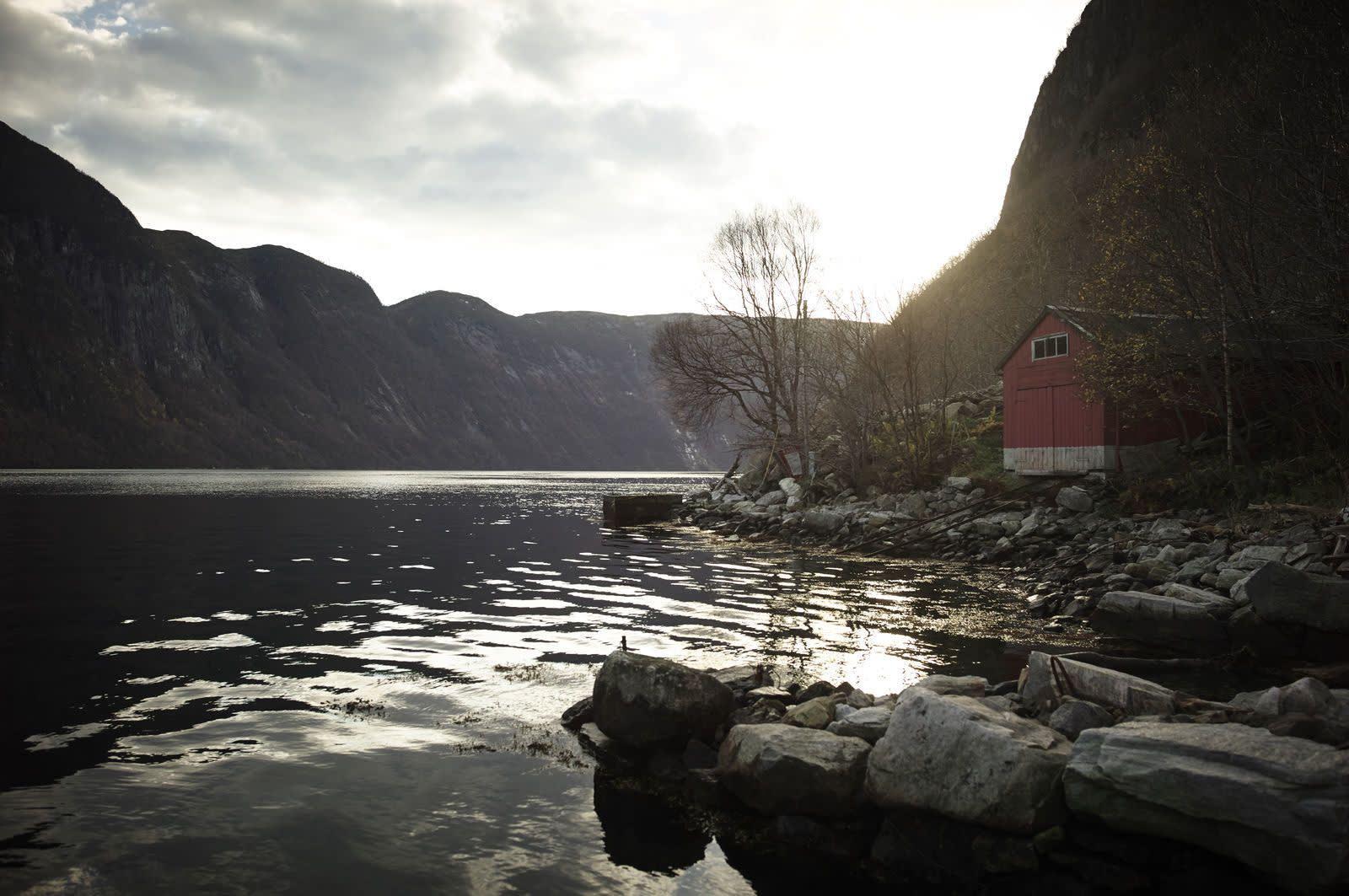 Et rødt naust ligger ved kanten av en fjord, omgitt av fjellvegger. Foto: Øivind Haug