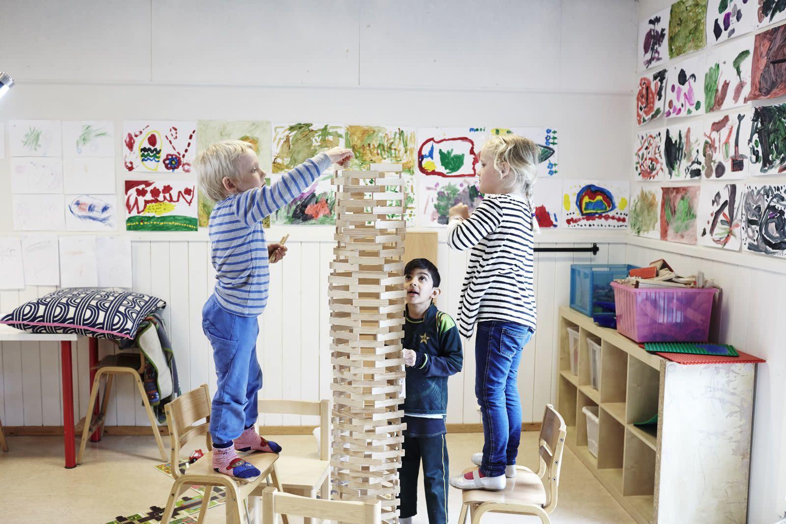 Tre barnehagebarn har bygd et tårn høyere enn seg selv. Foto: Øivind Haug