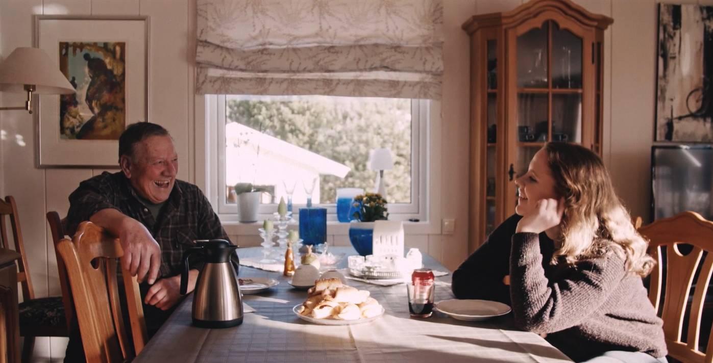 Ung jente og eldre mann sitter ved bord og prater.