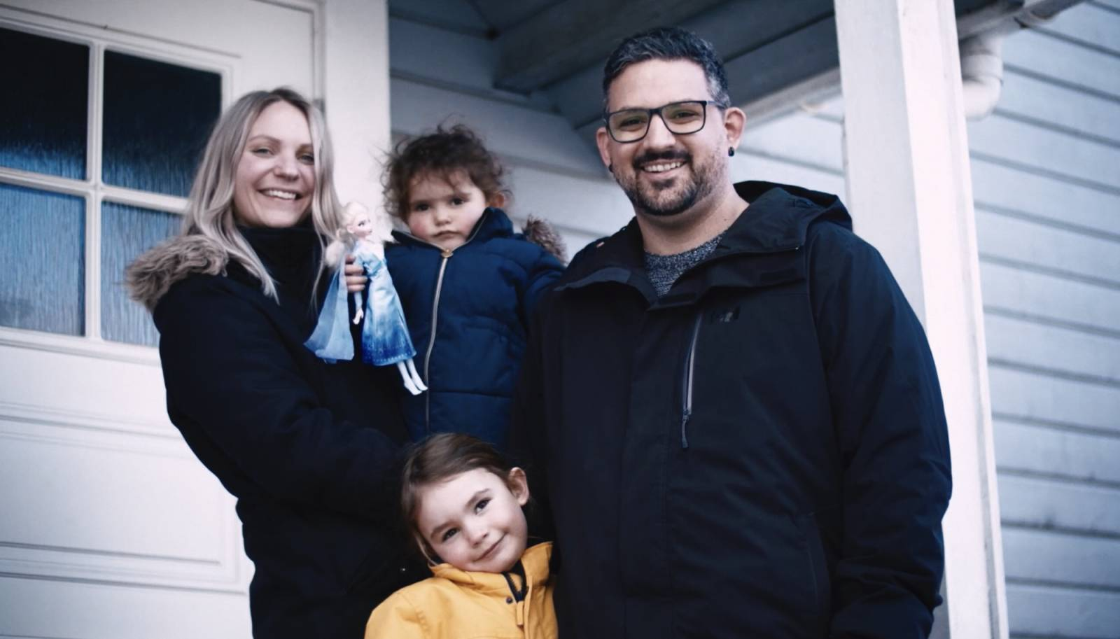 Familie på fire som står utenfor et hus. To barn, mann og kvinne.