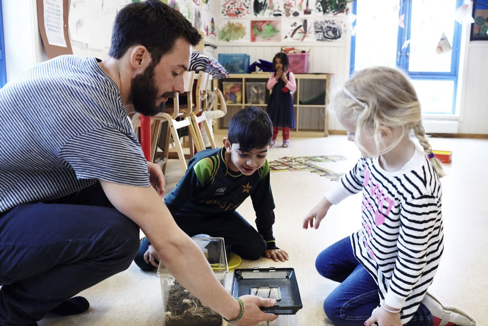 En barnehageansatt viser to energiske barn et herbarium. Foto: Øivind Haug