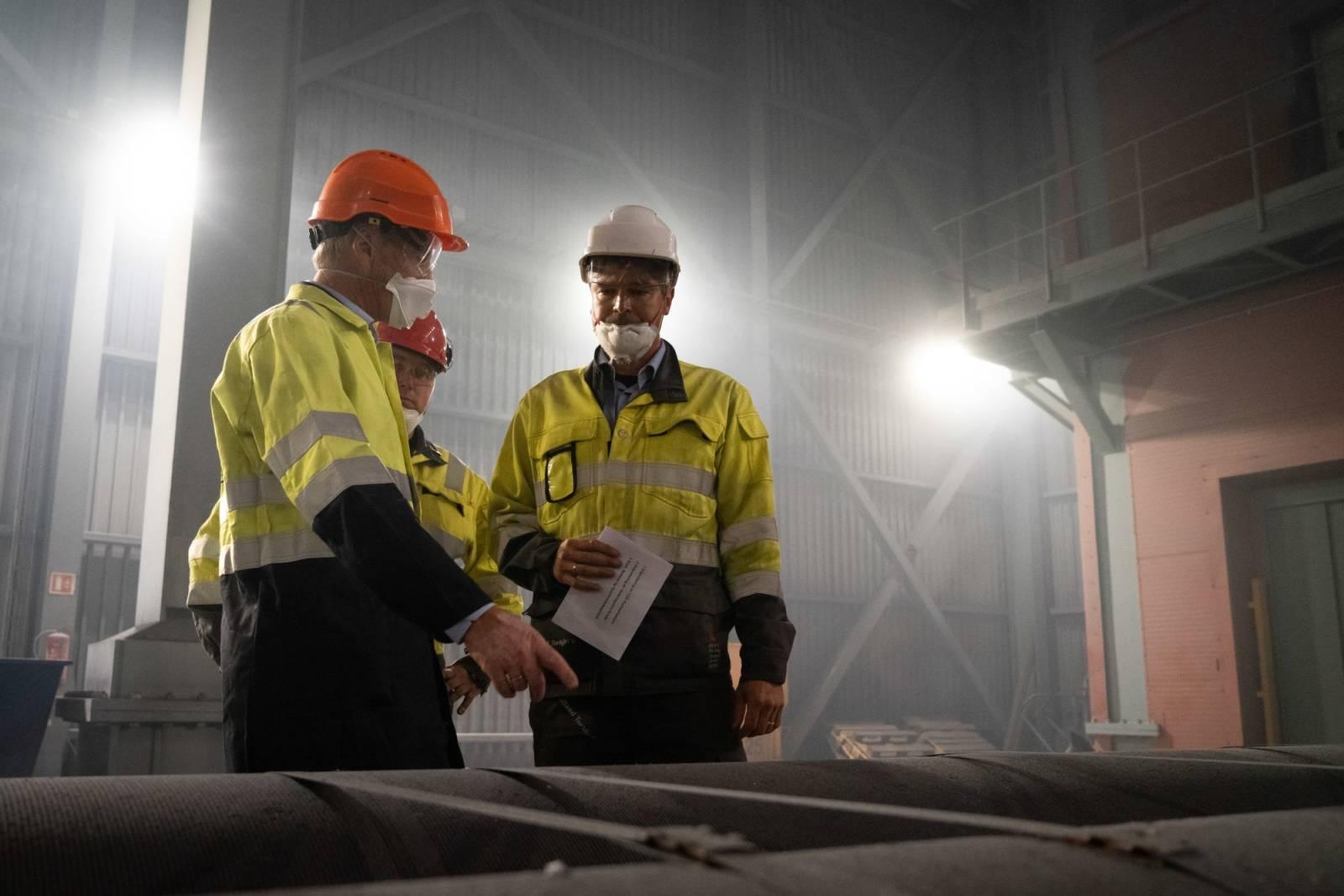 Industrihall hvor tre menn snakker sammen.