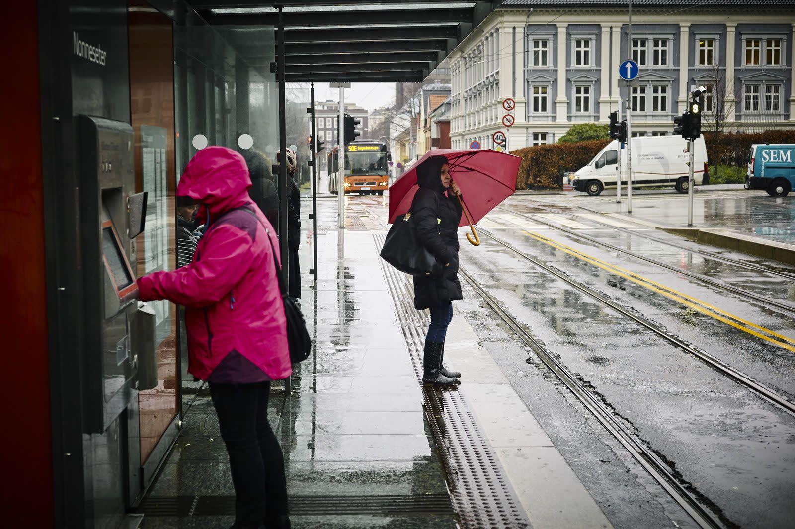 Noen mennesker står i ly av regnet og venter på bussen. Foto: Øivind Haug