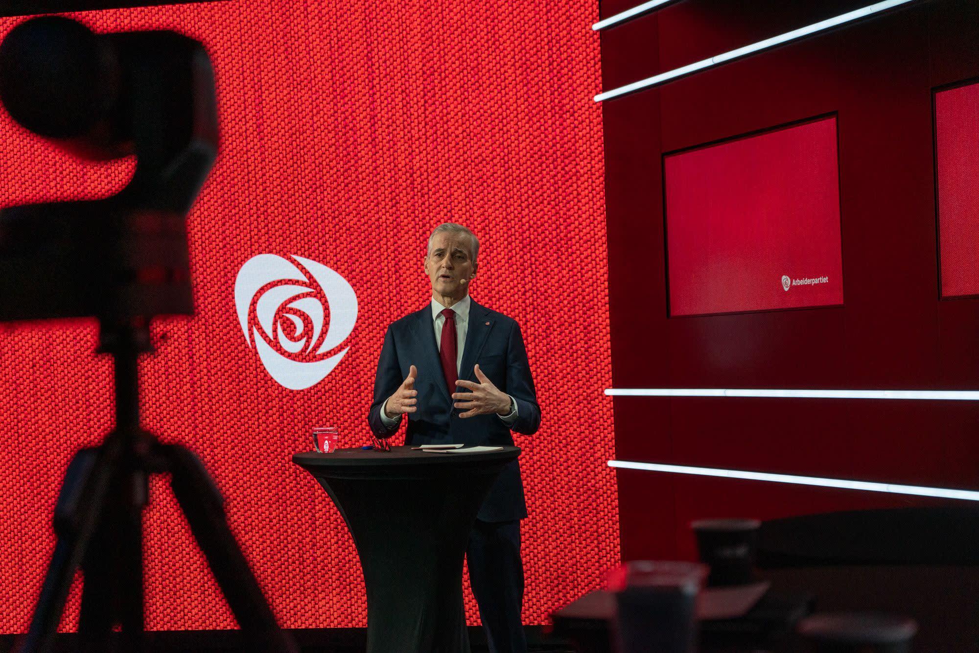 Jonas Gahr Støre bak ståbord foran rød vegg med Ap-rosen.