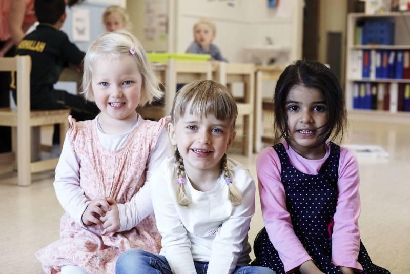 Tre venninner i barnehagen, de sitter på gulvet og smiler til kamera. Foto: Øivind Haug