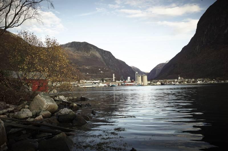 Oversiktsbilde av en bygd i enden av en fjord, industribygg ruver høyt foran fjellene, i forgrunnen ligger havet stille. Foto: Øivind Haug