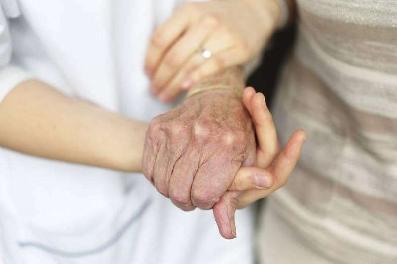 Nærbilde av en gammel og en ung hånd, den gamle støttes av den unge. Foto: Øivind Haug