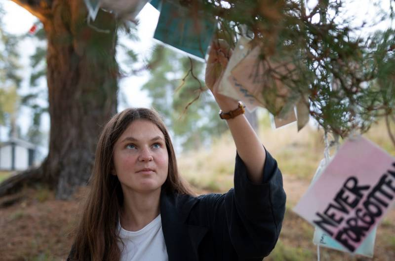 En jente leser på lappene som henger på verditreet på Utøya