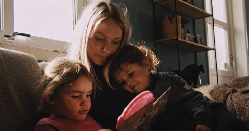 Mor sitter med to barn i sofa.