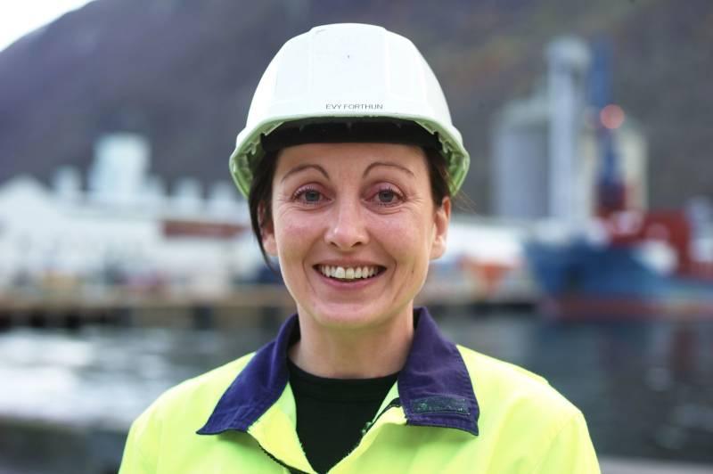 En kvinnelig industriarbeider står, ikledd arbeidsklær, foran et industriområde. Foto: Øivind Haug