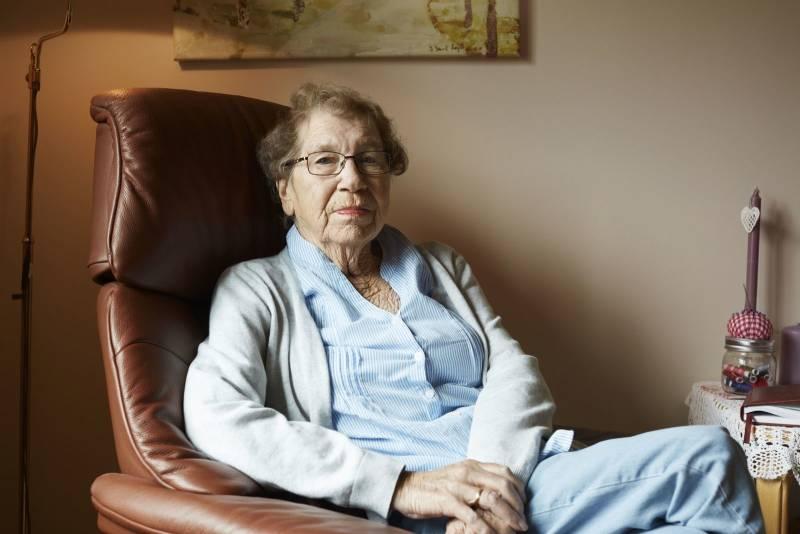 Portrett av en eldre kvinne som sitter i godstolen sin. Foto: Øivind Haug