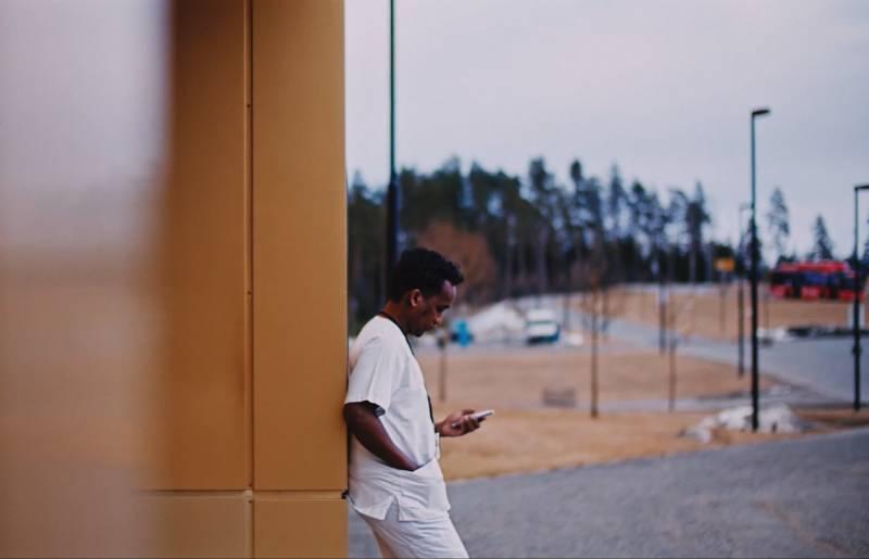 Mann som lener seg inntil en vegg og ser ned på mobilen.