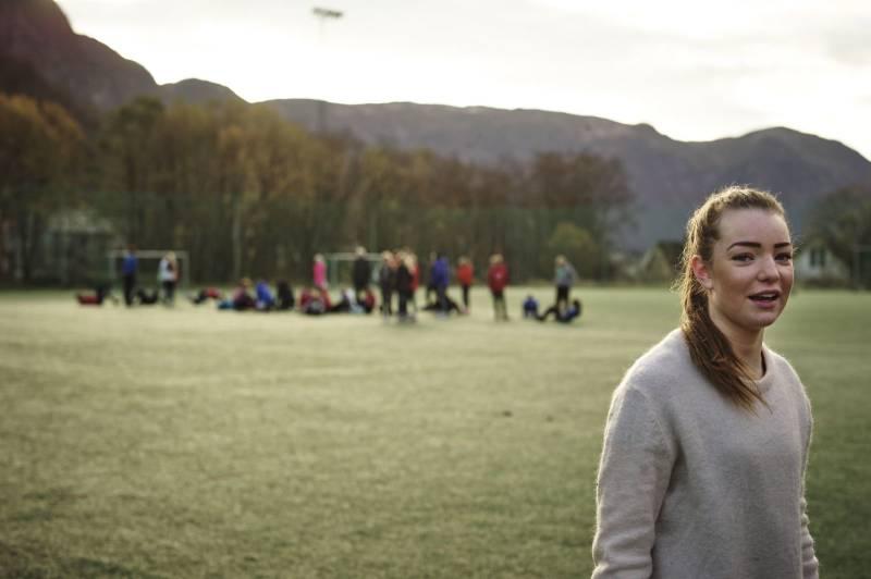 I forgrunnen ser vi en jente, i bakgrunnen står et fotballlag på banen. Foto: Øivind Haug