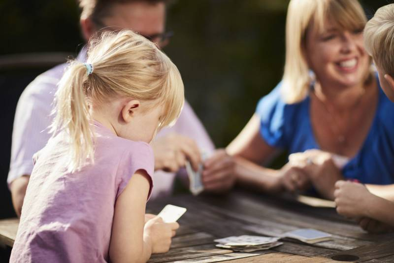 En familie på to barn og to voksne spiller kort utendørs. Foto: Øivind Haug
