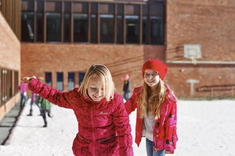 To rødkledde skolejenter leker og koser seg i skolegården. Foto: Øivind Haug