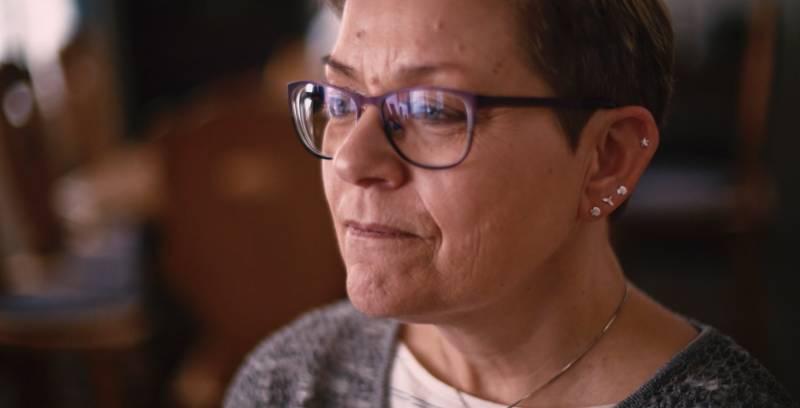 Dame med briller og kort år. Nærbilde av ansikt.
