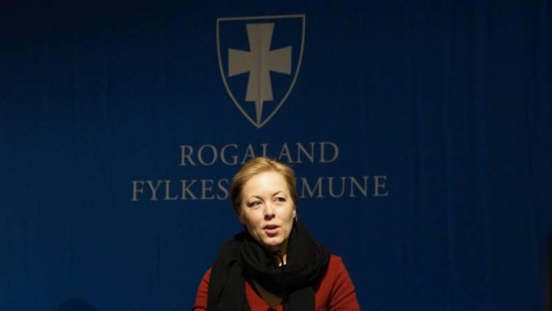 Fylkesvaraordfører Marianne Chesak på talerstolen foran Rogaland Fylkeskommune sin logo.