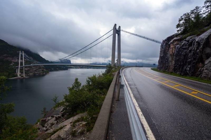 I forgrunnen ser vi en vei langs en fjord, og i bakgrunnen en flott bru over fjorden.