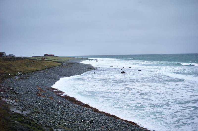 Rolige bølger slår innover en steinstrand. Foto: Øivind Haug