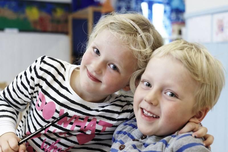 To barnehagebarn klemmer hverandre og smiler til kamera. Foto: Øivind Haug