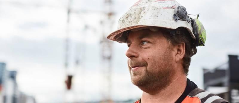 Anleggsarbeider med hvit hjelm smiler